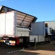 Carico e scarico di macchinario attraverso camion gru centinato con tetto ribaltabile